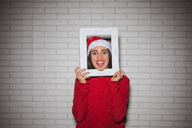 Cheerful woman showing tongue out in frame