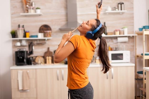 朝の台所で歌う陽気な女性