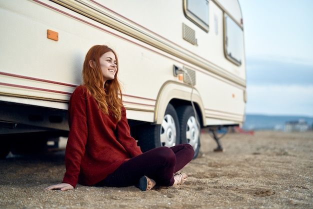Cheerful woman sits on the ground travel motorhome lifestyle