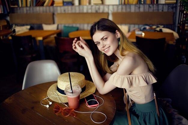 カフェコミュニケーションで飲み物を飲みながらテーブルに座っている陽気な女性。高品質の写真