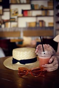 カフェファッションで飲み物と一緒にテーブルに座っている陽気な女性