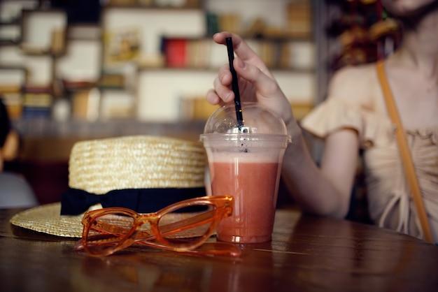 카페 패션으로 음료를 마시며 테이블에 앉아 있는 쾌활한 여성