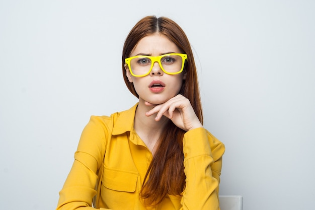 심장 노란색 셔츠와 함께 테이블 스틱에 앉아 쾌활 한 여자