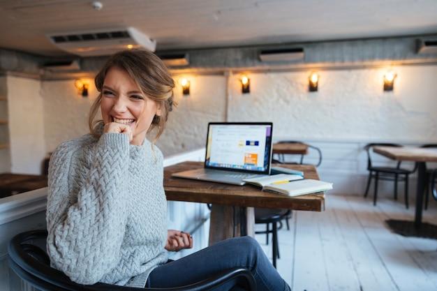 カフェでラップトップコンピューターとテーブルに座って、目をそらしている陽気な女性