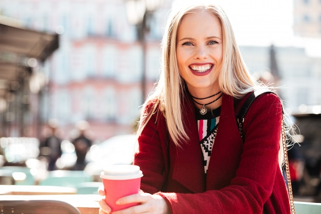 Cheerful woman sitting in cafe outdoors drinking coffee