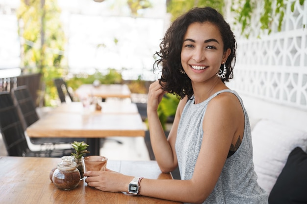 Cheerful woman sitting in cafe summer terrace