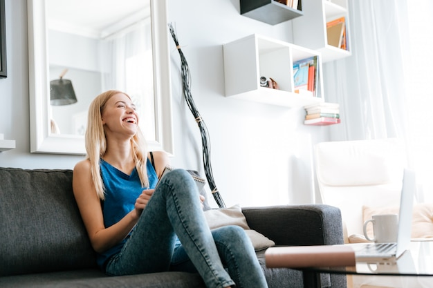 Cheerful woman sitting and laughing on sofa at home
