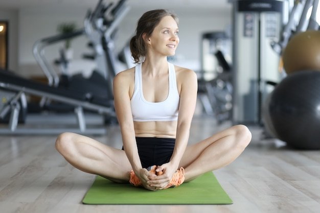Cheerful woman sitting on mat and smiling in gym