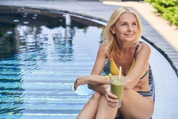 스무디를 마시고 따뜻한 날씨를 즐기는 동안 수영 설문 조사 근처에 앉아 쾌활한 여자