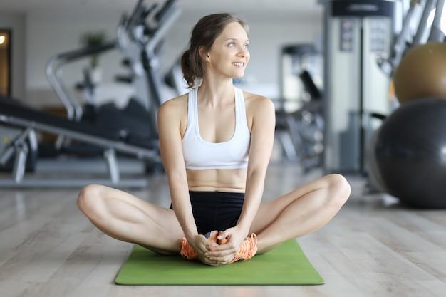 매트에 앉아서 체육관에서 웃 고 쾌활 한 여자