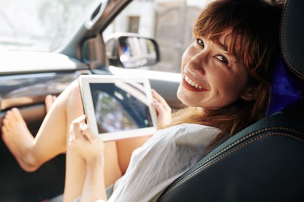 Веселая женщина, сидящая на пассажирском сиденье