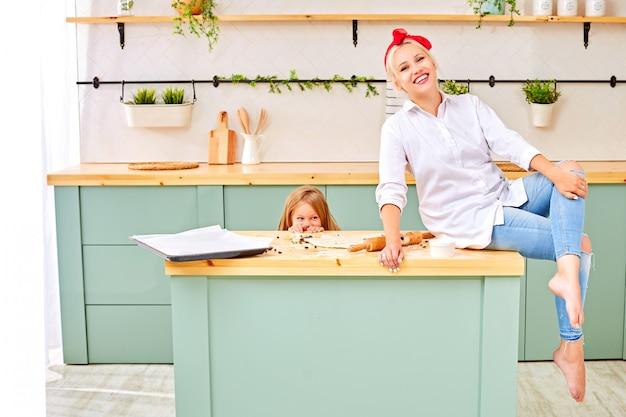 Cheerful woman sitting on table near hidden daughter