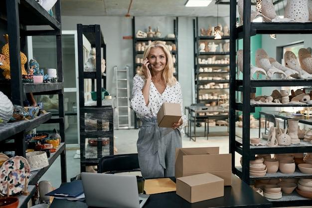 Веселая женщина, владелец малого бизнеса, улыбается в камеру, разговаривает по телефону
