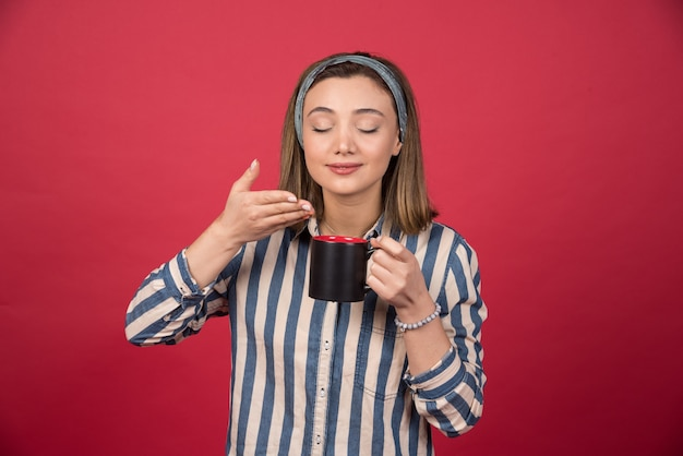La donna allegra odora l'aroma del caffè sulla parete rossa