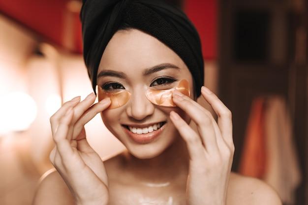 쾌활한 여자는 미소를 짓고, 그녀의 눈 아래에 금색 패치를 들고 앞을 들여다 본다.