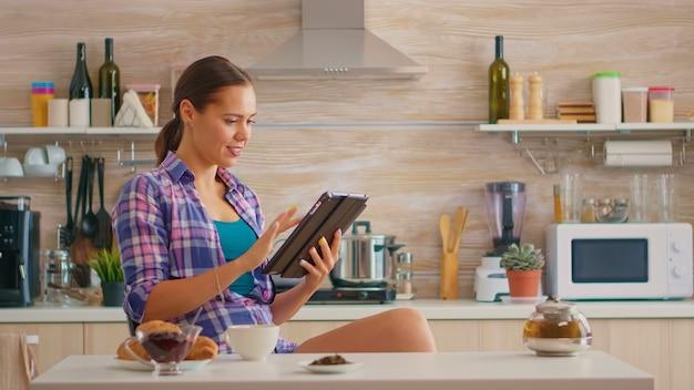 Жизнерадостная женщина улыбается и читает новости на планшете, попивая зеленый чай за завтраком. сидя за столом на кухне, работая дома, используя устройство с интернет-технологиями, набирая текст, просматривая на гаджете.