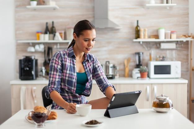 Веселая женщина улыбается и читает новости на планшете, попивая зеленый чай