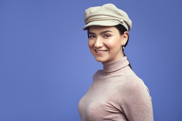보라색 벽에 스튜디오에서 포즈를 취하는 동안 웃 고 쾌활 한 여자