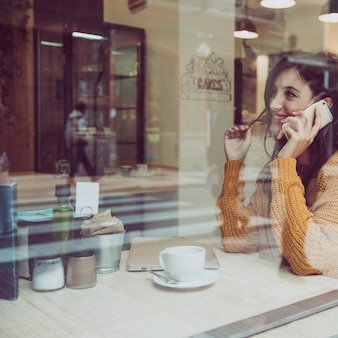 Cheerful woman speaking on phone in cafe