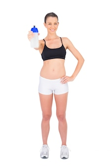 Cheerful woman in sportswear holding flask
