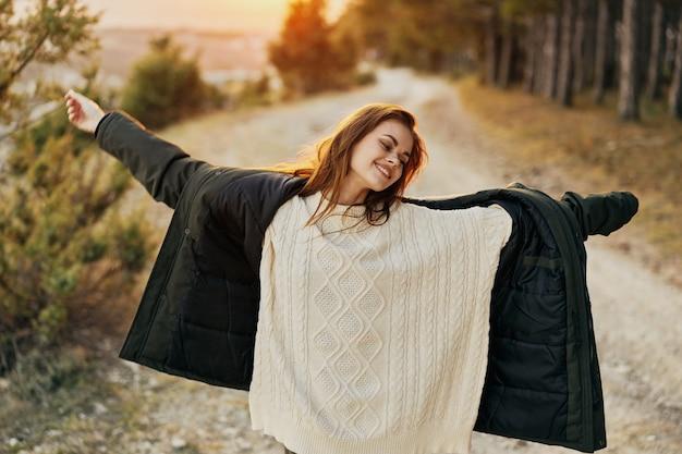Жизнерадостная женщина раскинула руки в стороны на открытом воздухе свобода свежего воздуха