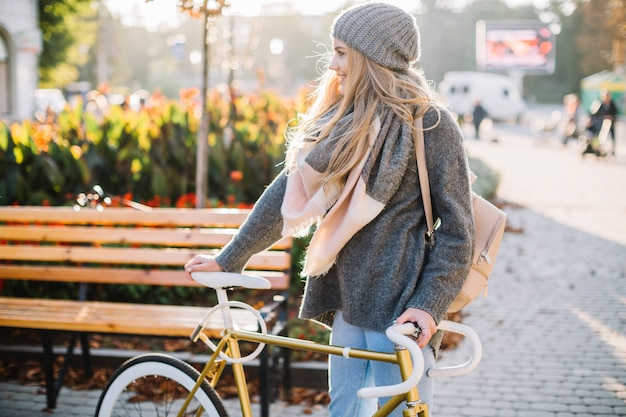 Cheerful woman standing near bicycle