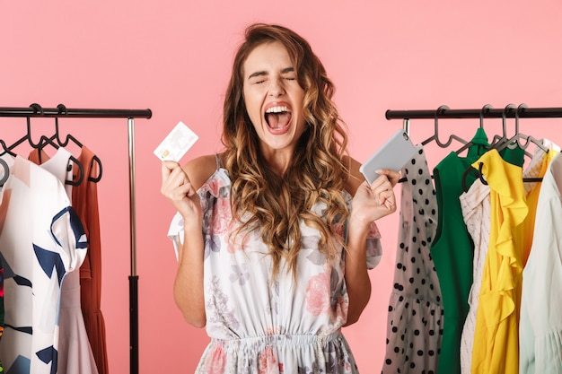 Cheerful woman standing near wardrobe while holding smartphone and credit card isolated on pink