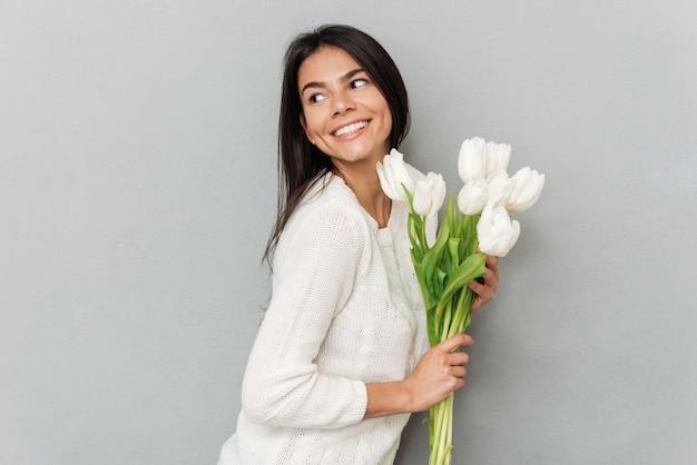 花と灰色の壁の上に立っている陽気な女性