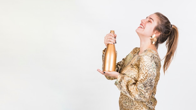 Cheerful woman standing with bottle of champagne