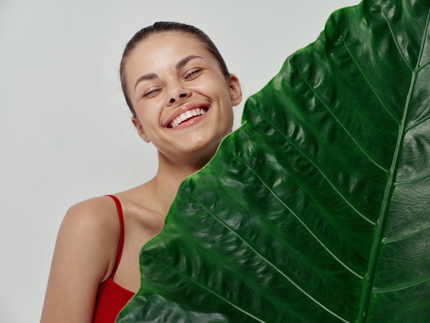Cheerful woman stands behind green leaf of palm tree clean skin model