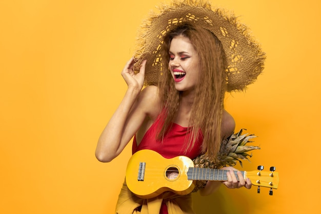 Cheerful woman in straw hat ukulele hands leisure lifestyle yellow