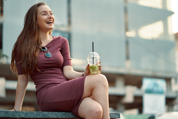 Cheerful woman in the street drinking morning refreshing drink