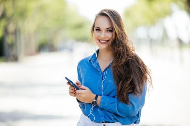 La donna allegra in strada usa il suo smartphone. giovane imprenditrice utilizzando il telefono in strada.