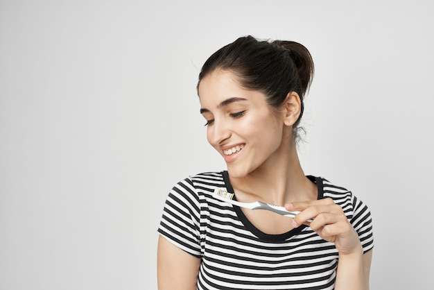 Cheerful woman in a striped tshirt toothbrush in hand isolated background