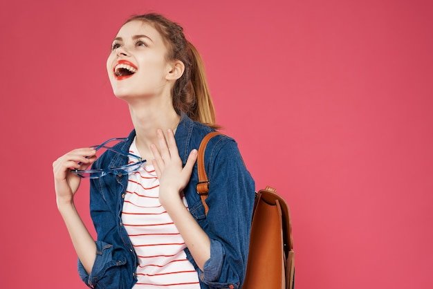 陽気な女性学生ファッショナブルな服のバックパックティーンエイジャー