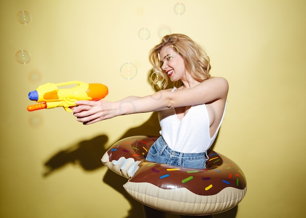 Cheerful woman in summer clothes having fun with water gun
