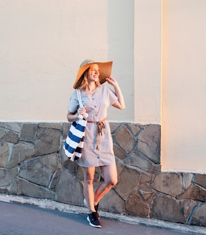 Cheerful woman in summer clothes walking on the street holding her hat in sunset light
