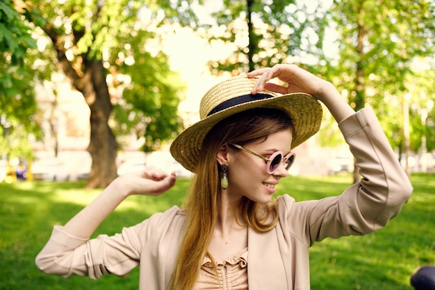 Cheerful woman in sunglasses outdoors in the park in summer walk.