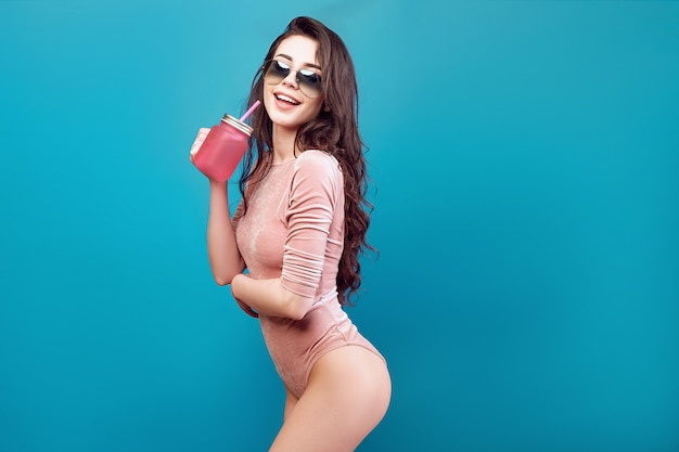 Cheerful woman in sunglasses with drinking jar