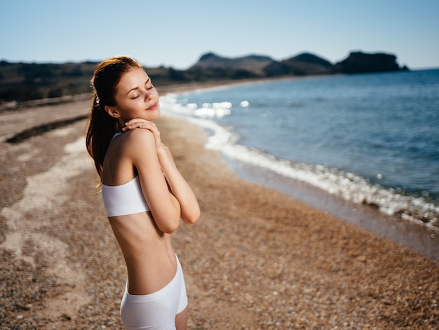 Cheerful woman in swimsuit in the morning on the island exotic travel fresh air