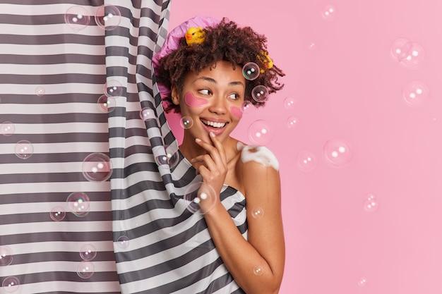 陽気な女性がバスルームでシャワーを浴びて自分で洗うボディに発泡ジェルを塗りますカーテンの後ろに隠れてシャボン玉でピンクの壁に隔離されて目をそらします