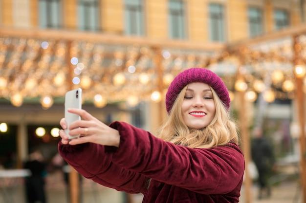 花輪のある通りで自分撮りをしている陽気な女性