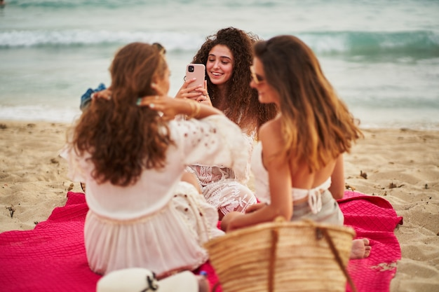 Cheerful woman taking selfie to her friends on a red towel at beach