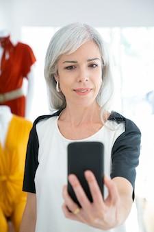 패션 스토어에서 쇼핑하는 동안 스마트 폰에 selfie를 복용하는 쾌활 한 여자. 중간 샷, 전면보기. 부티크 고객 또는 커뮤니케이션 개념