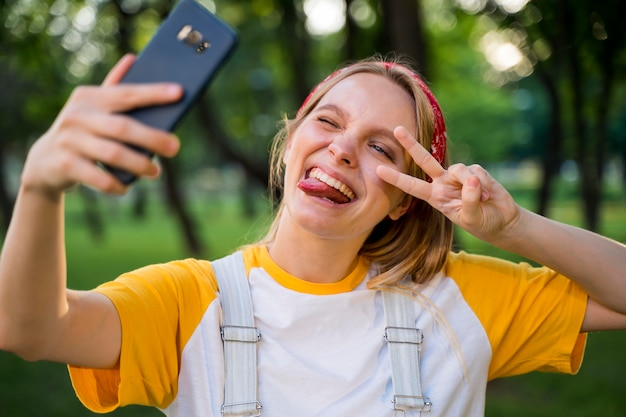 Cheerful woman taking selfie outdoors