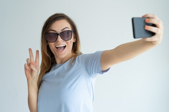 Cheerful woman taking selfie photo on smartphone. Happy lady showing victory sign.