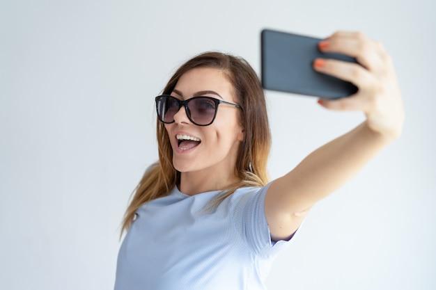 Cheerful woman taking selfie photo on smartphone