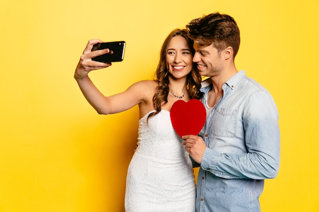 Cheerful woman taking selfie on smartphone with her attractive boyfriend holding red heart