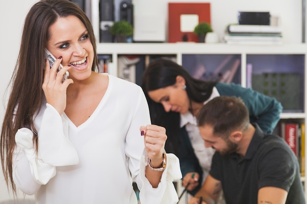 Cheerful woman talking on phone and celebrating