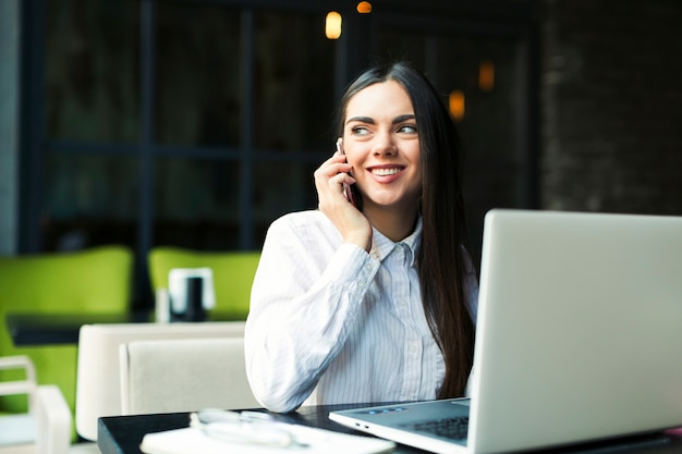 Cheerful woman talking on phone at laptop
